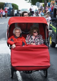 Carmel O Flaherty pedaling Maura and Marie Cotter during the Cultural Parade as part of the annual Festival Of Fun in Kilmihil. Photograph by John Kelly