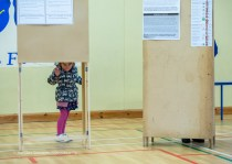 Little Alannah Cahalane peeps out from behind a polling booth during voting in the General Election 2020 at Corofin school. Photograph by John Kelly.