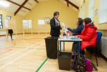 Voter Mary Lillis collects her ballot paper from Presiding Officer Bridget Rynne and Poll Clerk Aisling O Loughlin during voting in the General Election 2020 at Corofin school. Photograph by John Kelly.