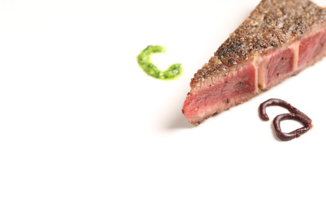 "One corner of appetizing bison steak with the letter ""a"" next to the right edge of the meat and the letter ""c"" next to the left edge of the piece"
