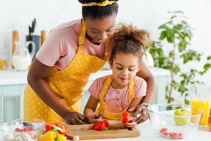 mom helping kid prepare food
