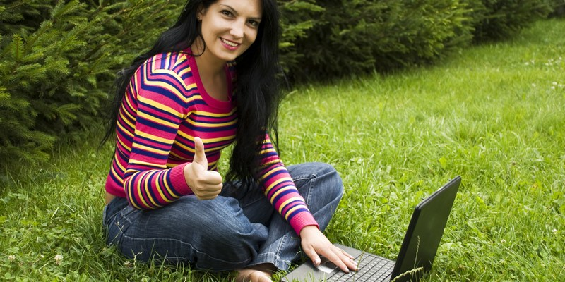 Woman in nature with laptop giving thumbs up