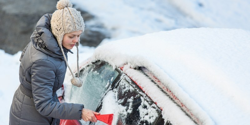 woman cleaning snow and frost from car