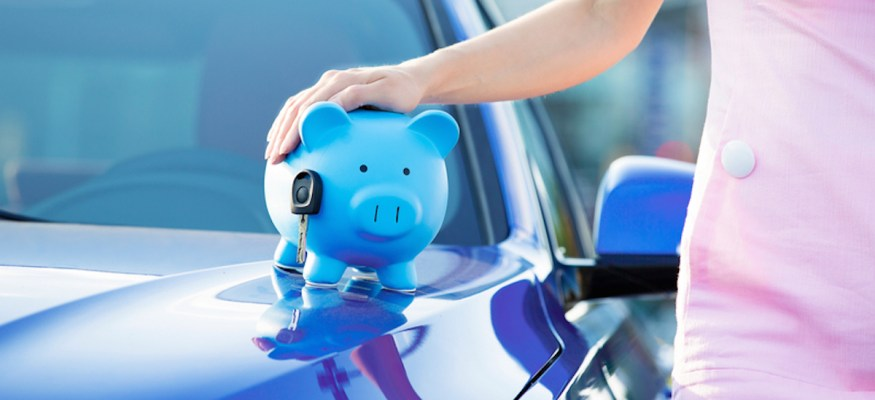 woman with piggy bank standing next to a car