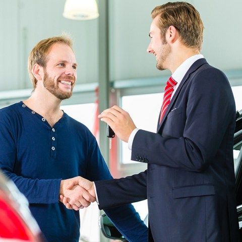 Young man and seller with auto in car dealership