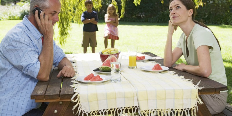 A father receiving a business call during a family lunch in the garden