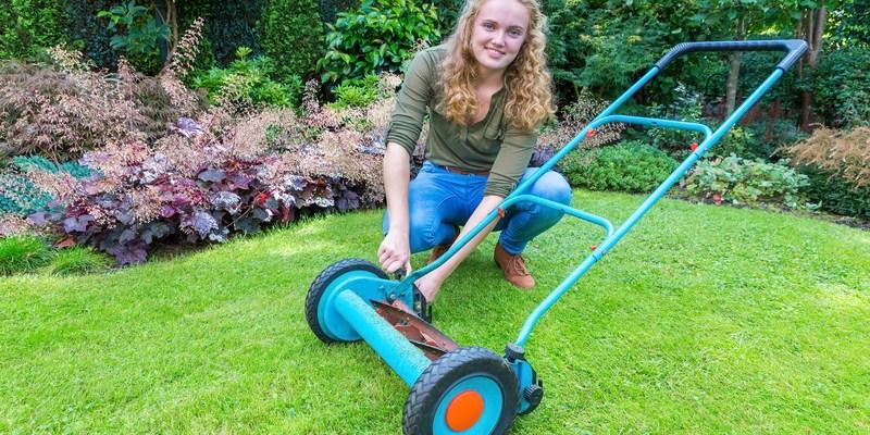 European teenage girl fixing lawn mower on green grass