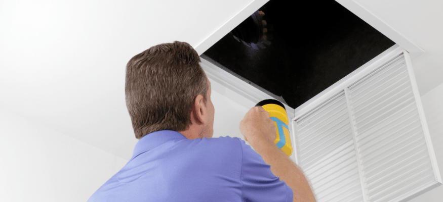Male looking up into a ceiling air intake duct with a flashlight checking for maintenance. Person with a flashlight examining with a square opening of a home HVAC system