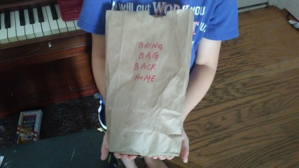 child holding paper bag
