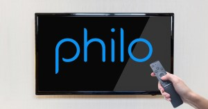 philo streaming service projected onto a TV screen while a hand holds a remote in front of the screen