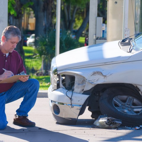 auto insurnace adjuster inspecing auto insurance claim