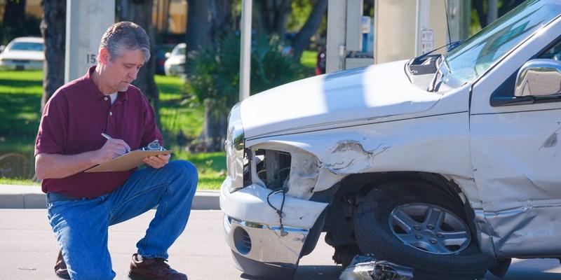 auto insurnace adjuster inspecing auto insurance claim
