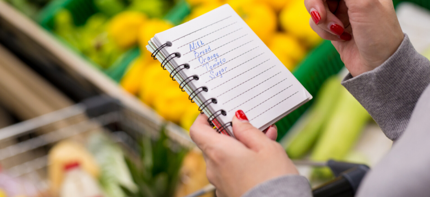 Woman with notebook in grocery store, closeup. Shopping list on paper
