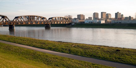 The streets and buildings of Dayton Ohio only have a few travelers early Sunday morning Mad River flowing by