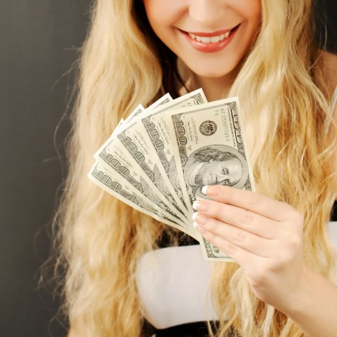Woman holding $500 in cash