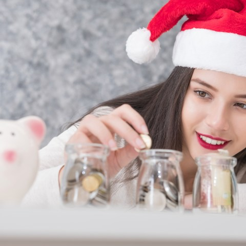 Woman saving money for Christmas with Santa hat on