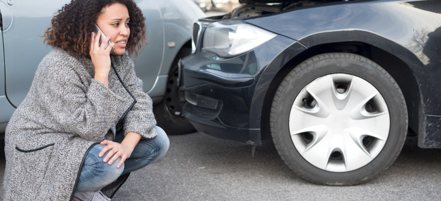 Woman calling emergency help after a car accident