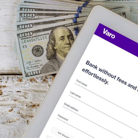 Varo Bank on tablet sitting on $100 bills