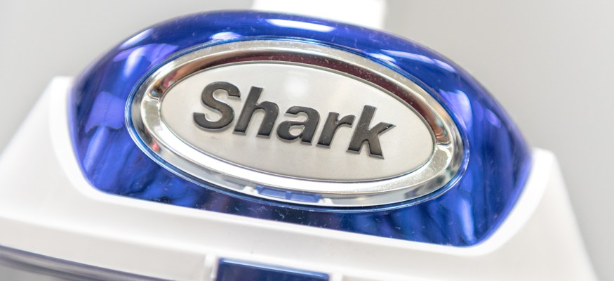 A blue and white Shark Vacuum on a store display.