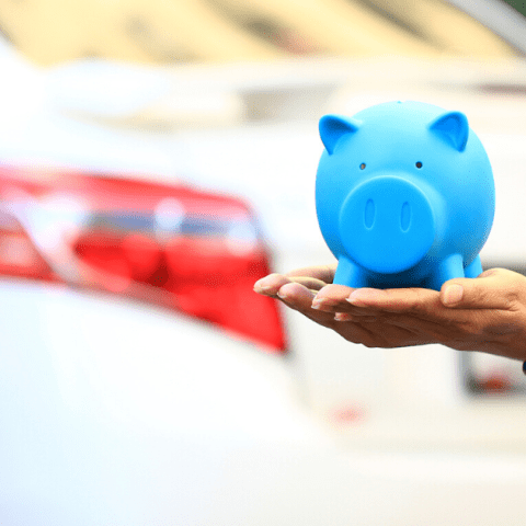 Saving money and loans for car concept, Young woman holding blue piggy with standing at the car parking lot background, Auto.