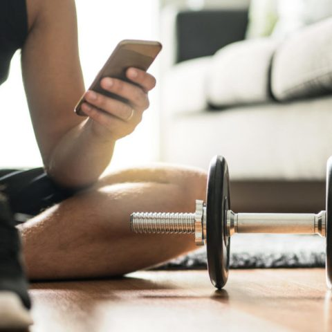 A man using a free workout app to exercise at home