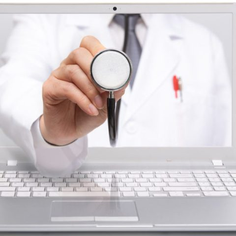 A doctor reaching through a computer to symbolize telemedicine and telehealth