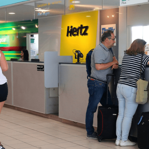 Customers at rental car counter at airport featuring Enterpresie, Hertz and Avis brands