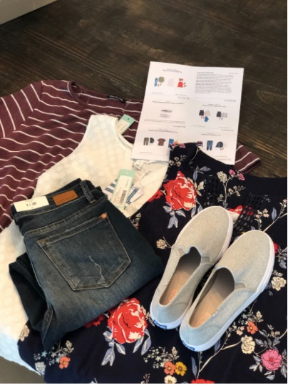 Stitch Fix clothing including three shirts, a pair of jeans, a pair of shoes and a set of instructions.