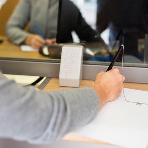Bank customer fills out application at window