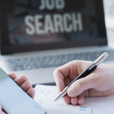 Man searching laptop for remote entry-level jobs online