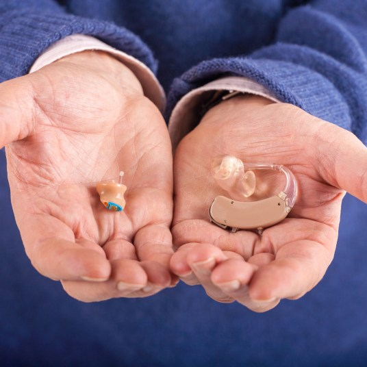 CIC and BTE hearing aids in a man's hands
