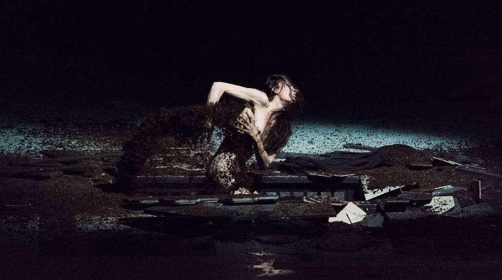 Jeanne au bûcher dans la mise en scène de Roméo Castellucci. Audrey Bonnet (Jeanne) creuse sa propre tombe