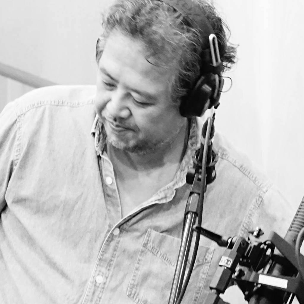 Recording engineer Ricardo Marui wearing headphones in front of a microphone