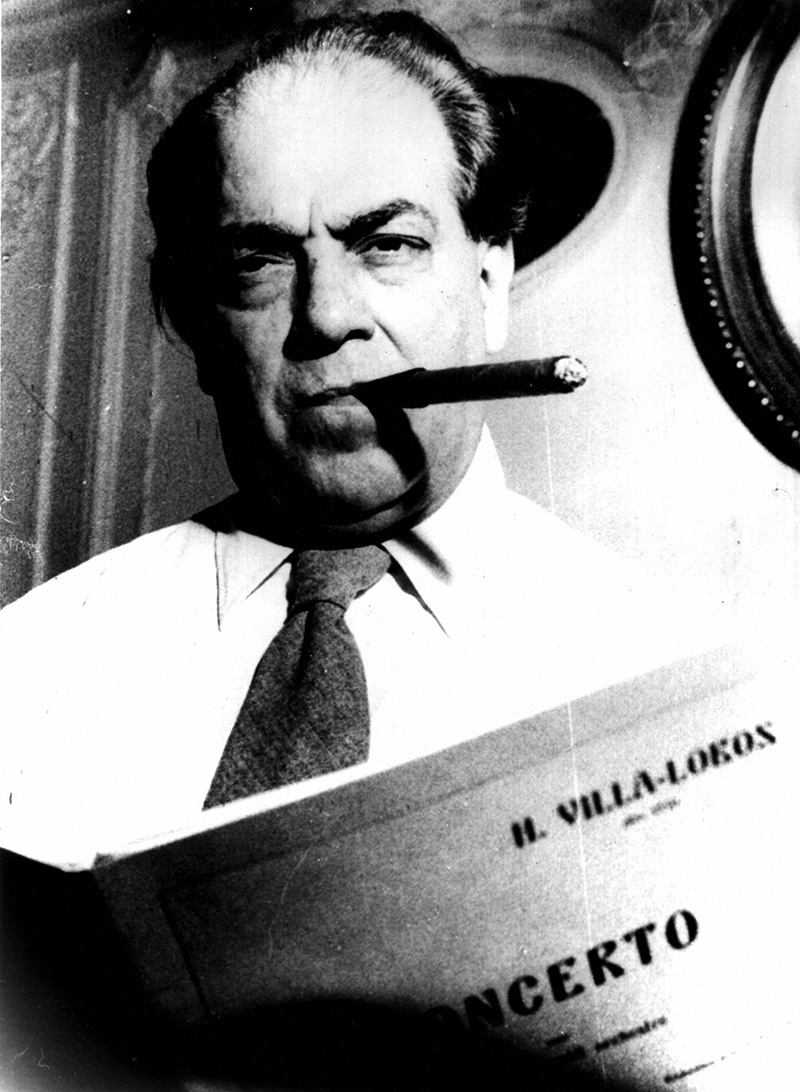 Composer and classical guitarist Heitor Villa-lobos smoking a cigar and holding a score of his concerto
