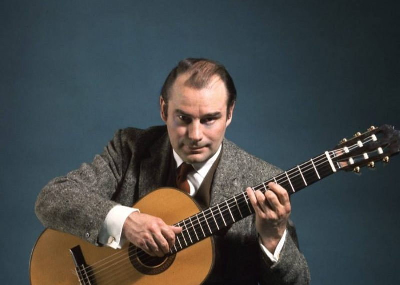 classical guitarist julian bream playing guitar looking at camera