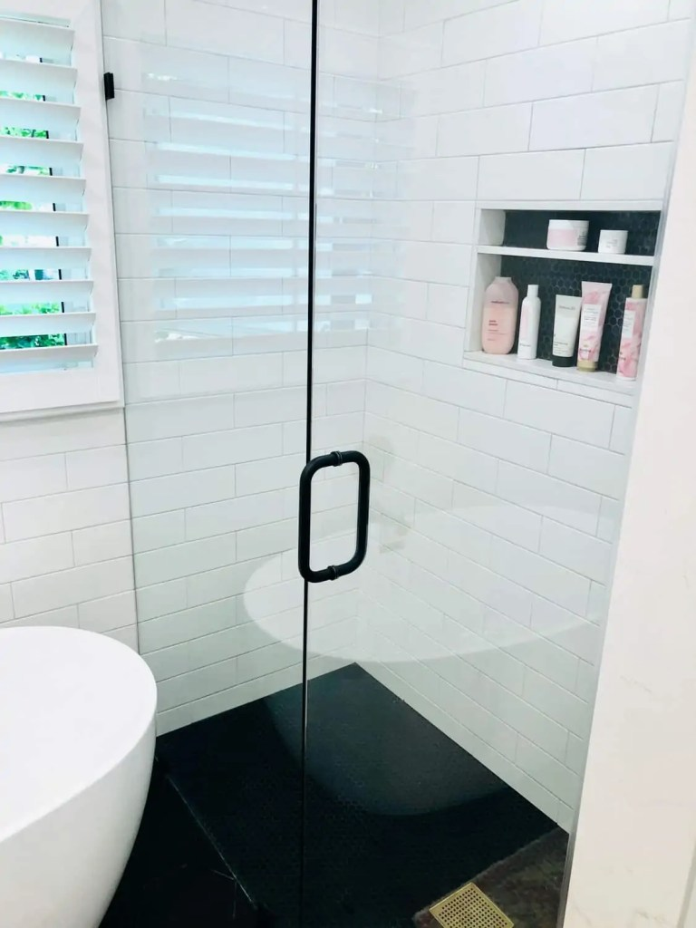 black penny tile in shower and wall niche