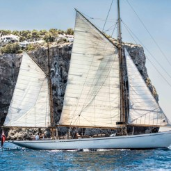 gaff ketch Owl sailing with cliff behind