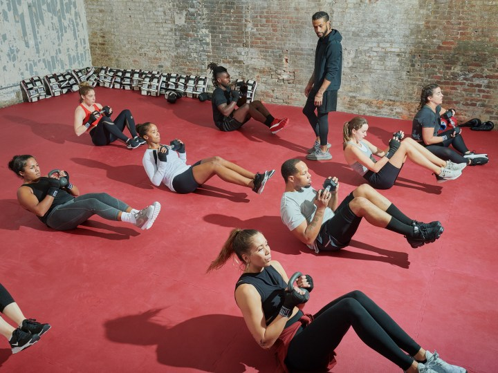 Group fitness class working abs with personal trainer in gym