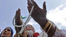 Kashmiri Muslim devotees pray as an unse