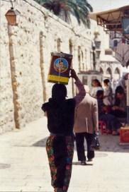 Femme bédouine transportant une boîte sur sa tête