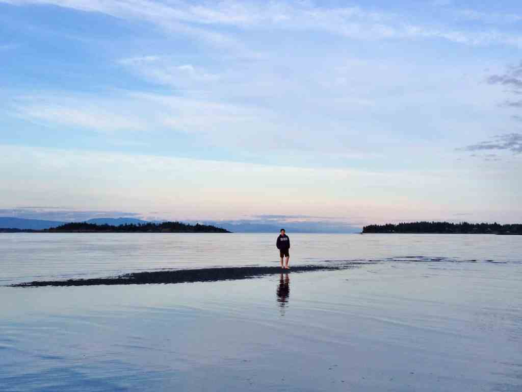 boy standing on rathtrevor beach parksville