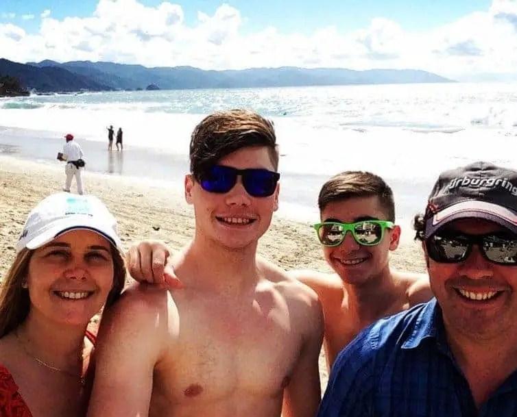 family of four posing on beach in puerto vallarta mexico