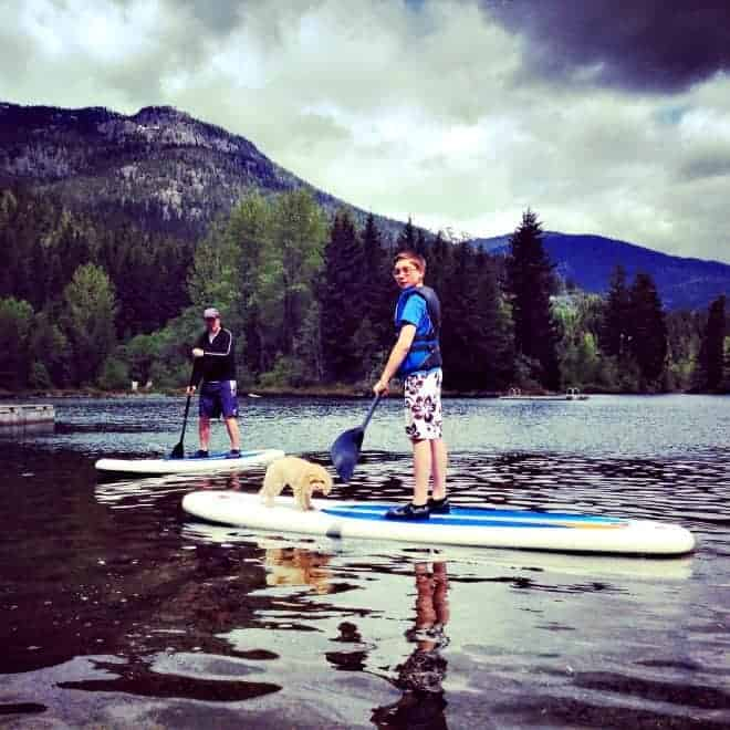 boy and dog on stand up paddle board in whistler with kids