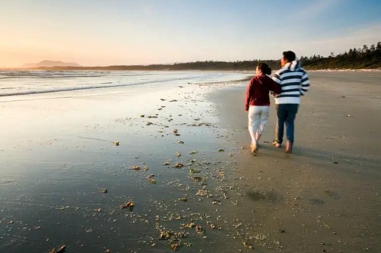 couple walking along beach in bc