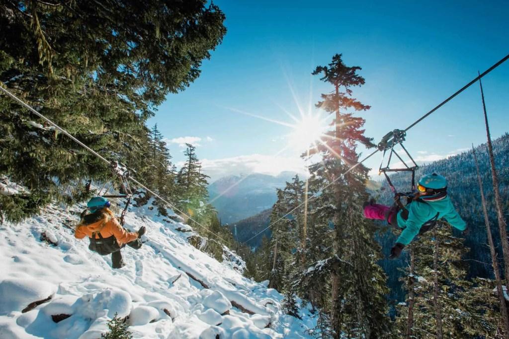 people zip lining in whistler in winter