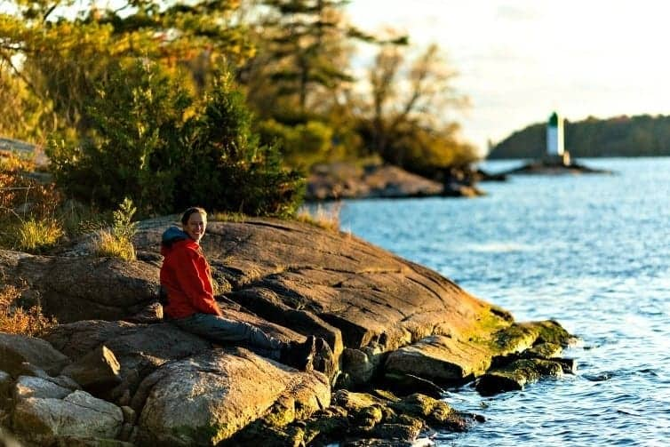 lady sitting on rock on lakeshore in ontario
