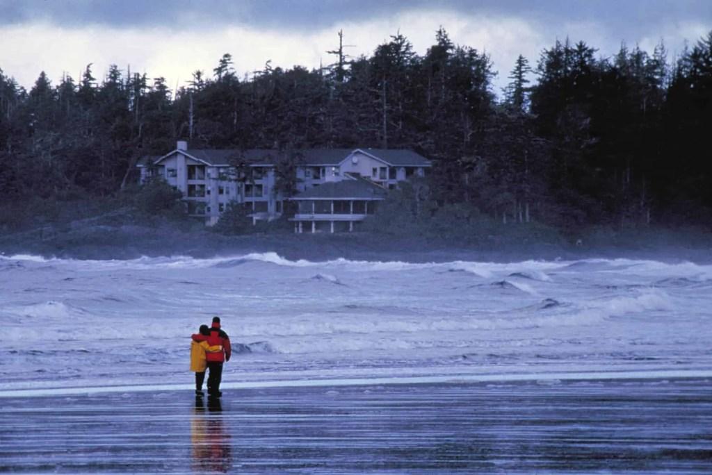 couple walking along beach in tofino