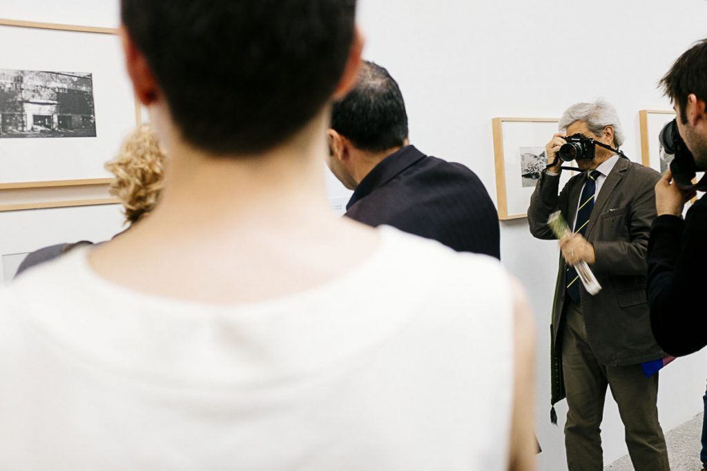 Bernard Plossu fotografiando a Manuela Carmena en su propia inauguración. © Ana Zaragoza