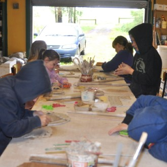 Rolling out clay and cutting out shapes