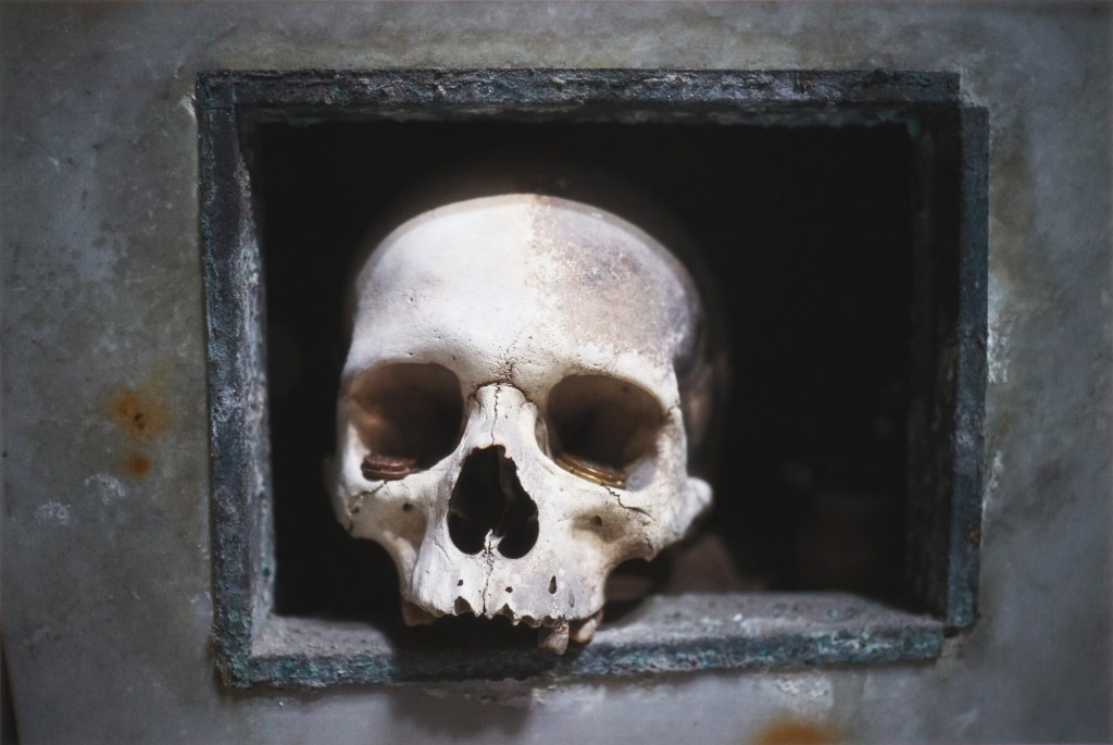 Human skull with coins in its eye sockets kept by the anime pezzentelle cult at the Cimitero delle fontanelle ossuary in Napoli Italy.